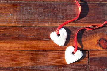 Two cookies in the form of hearts with red ribbons on brown wooden boards