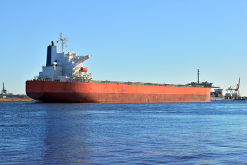 Large cargo ship (Bulk carrier) sailing in a bright sunny day. R