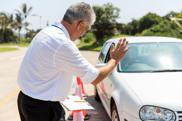 Fototapete - senior instructor teaching learner driver to park a car