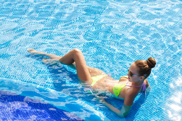 Beautiful woman with sexy body by the pool