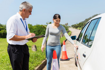 Fototapete - female learner driver with instructor doing pre driving inspecti
