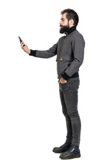 Serious stylish punker in gray jacket taking selfie photo. Side view. Full body length portrait isolated over white studio background.