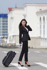 Brunette with valise. Girl in black suit with rolling suitcase