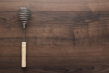 retro egg whisk with wooden handle on brown table with copy space