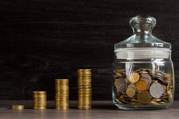 Moneybox with gold coins on wooden background
