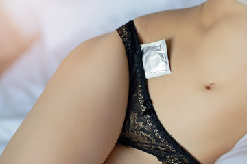 Close-up of woman with condom packet in black underwear