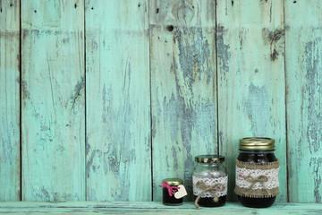 Glass jars of jam on mint green wood shelf