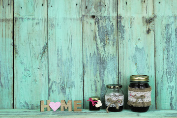 Home sign with heart by glass jars of jam on mint green wood shelf