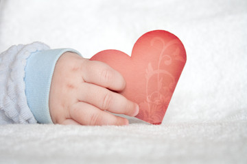 Heart shaped card in baby hand