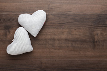 two knitted heart shapes on the wooden table