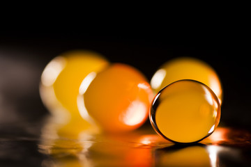 Abstract composition with beautiful, round jelly balls on an aluminium foil with reflexions and dark background