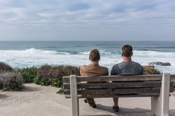 Father and Son Sit on Bench Looking Out at The Ocean