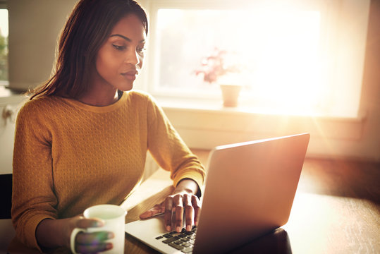 Woman checking her computer and holding coffee cup