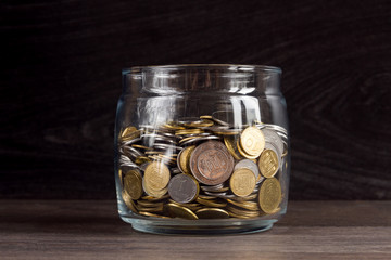 Moneybox with gold and silver coins on wooden background
