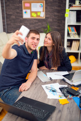 Happy businesswoman taking selfie with male colleague in meeting room at creative office