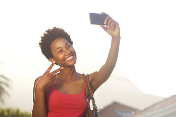 Young woman gesturing peace sign and taking a selfie