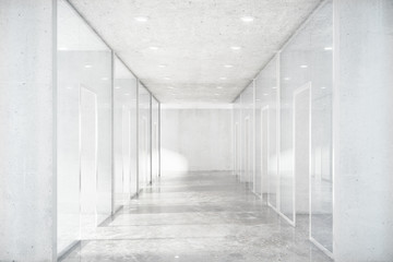 Long corridor with concrete floor and transparent walls in moder