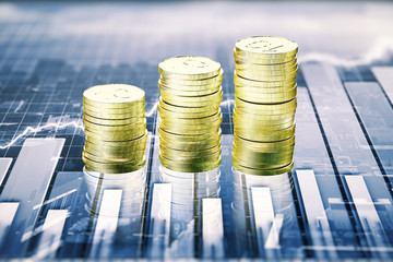 Stacks of gold coins on the table with business graph