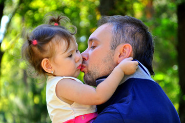 Father kissing his little daughter happy
