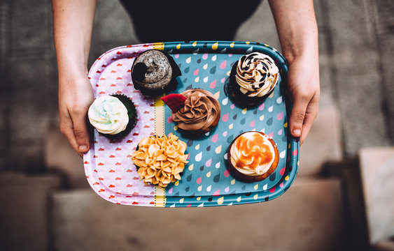 Woman Holding a Tray with Cupcakes