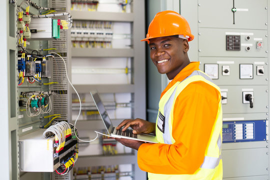 african electrical worker using laptop computer