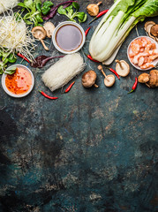 Asian cooking ingredients: rice noodles, pok choy , sauces, shrimps, chili and Shiitake mushrooms on dark background, top view, place for text. Asian food concept: Chinese or Thai cuisine.