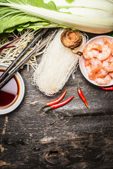Ingredients for asian cooking: rice noodles, Bok choy (chinese cabbage) , soy sauce, shrimps, chili, and chopsticks on vintage rustic background, top view, place for text. Asian food concept.
