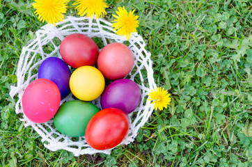 Bowl of painted decoupage Easter eggs on the grass