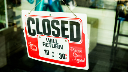 Vintage retro looking Closed sign in a shop showroom with reflec