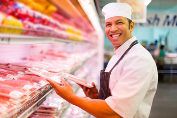 mid age butcher organizing meat products
