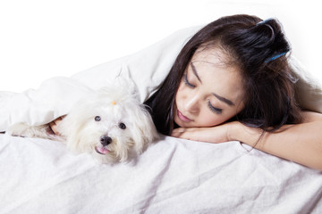 Cute woman sleeping with dog on bed