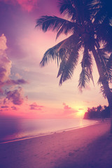 Fototapete - Beautiful tropical beach with silhouettes of palm trees at sunse