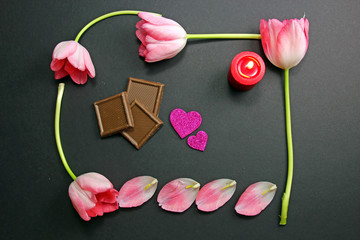 A pink Tulip frame with a candle, chocolates and two pink hearts