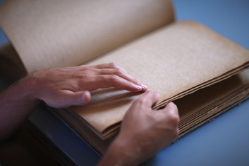 Tactile book for blind readers, hands in focus