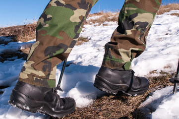 Low section side view of an unrecognizable man hiking on the snow