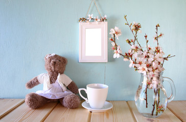 cute teddybear, cup of coffee and blank frame next to spring white cherry blossoms tree