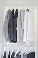 row of white, gray, black shirts with pants hanging in wooden wardrobe