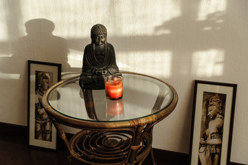 Buddha statuette on the table on the background wall with shadows.