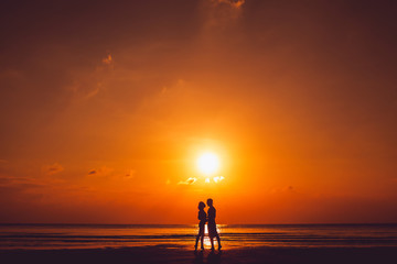 cute young beautiful couple posing on the beach at sunset, kissing his girlfriend softly on the forehead, hipster style, happily smiling in sunglasses on a tropical island,outdoor portrait, closee