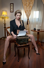 Attractive sexy blonde woman with black bra posing provocatively sitting on chair typing on typewriter. Beautiful woman with long legs on high heels wearing black jacket over lingerie in vintage room