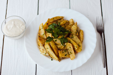 beautiful roasted potatoes with herbs and spices on a white plate