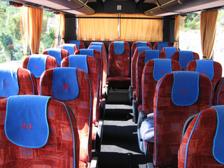 Bus interior. Red and blue seats. Cheap travel bus.