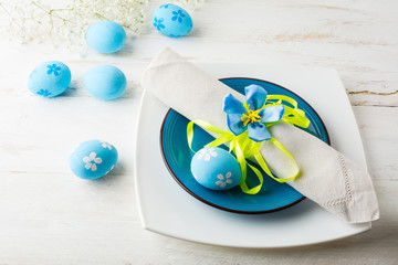 Blue Easter table place setting with plate, napkin and Blue Decorated Easter eggs on white wooden background