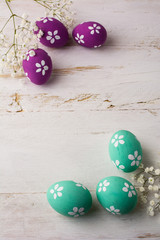 Pale turquoise and Pink Decorated Easter eggs on a white wooden background, vertical, space for text, copy space