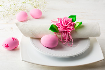 Pink Easter table place setting with plate, napkin and Pink Decorated Easter eggs on white wooden background