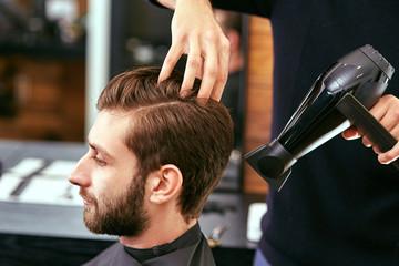 drying, styling men's hair in a beauty salon