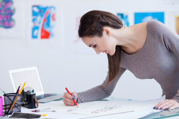 Pretty female photo artist draws a picture
