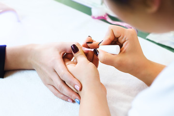 Close-up of beautician applying colorful varnish
