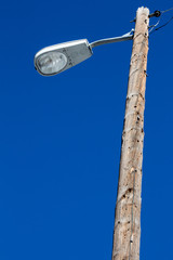 Street light with wooden post against blue sky