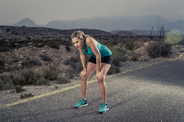 young exhausted sport woman running outdoors on asphalt road breathing